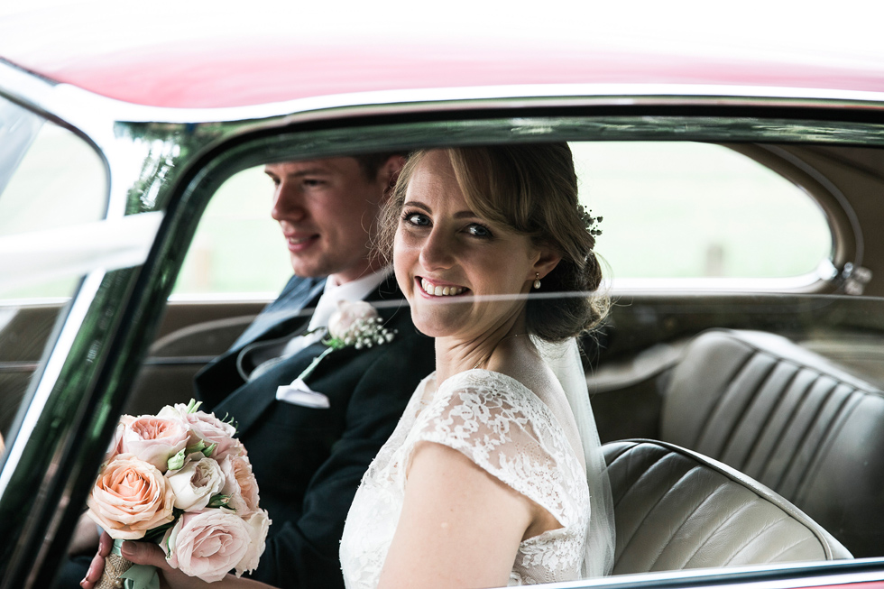 Bride and groom in a jaguar car