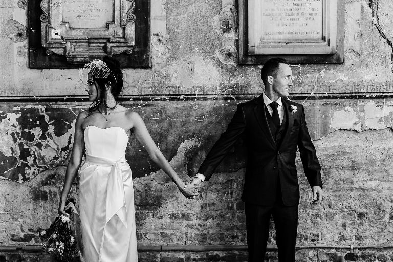 Bride and groom against a beautiful wall in London