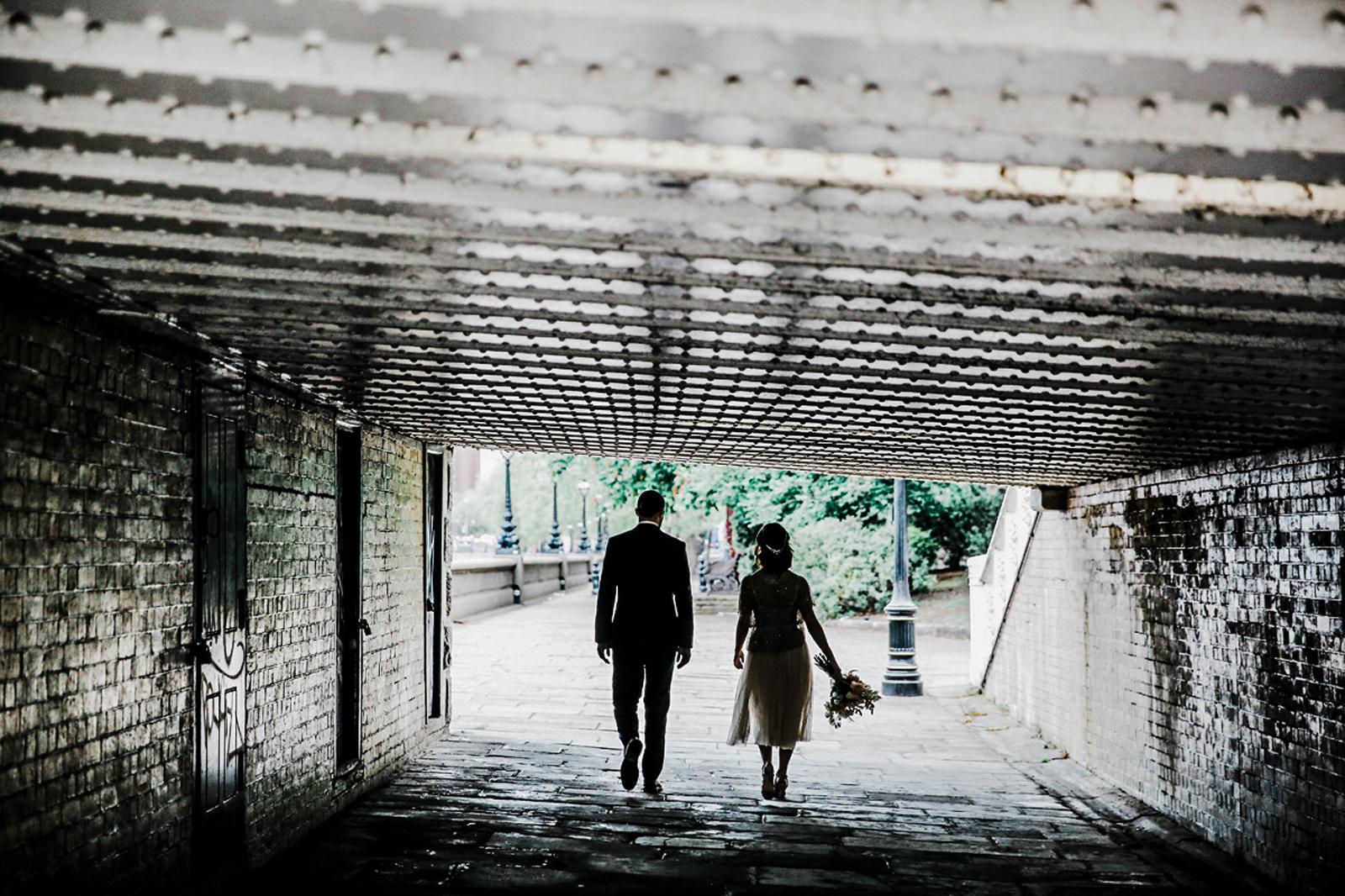 bride and groom walking through Chelsea bridge