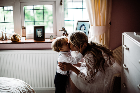 Bride kissing her baby on her wedding day