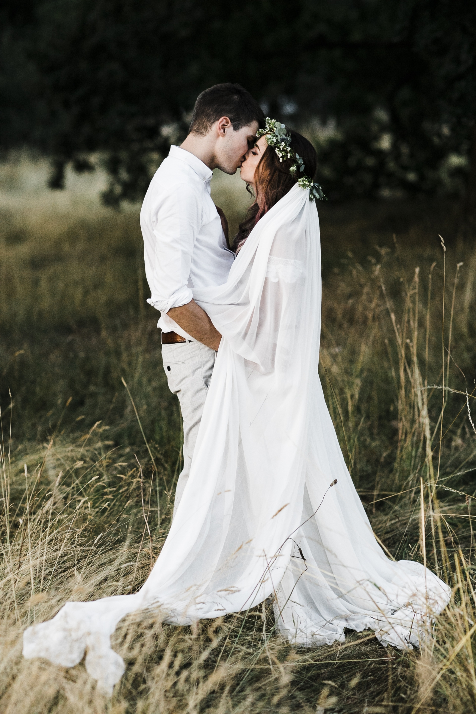 Bride and groom in a field kissing