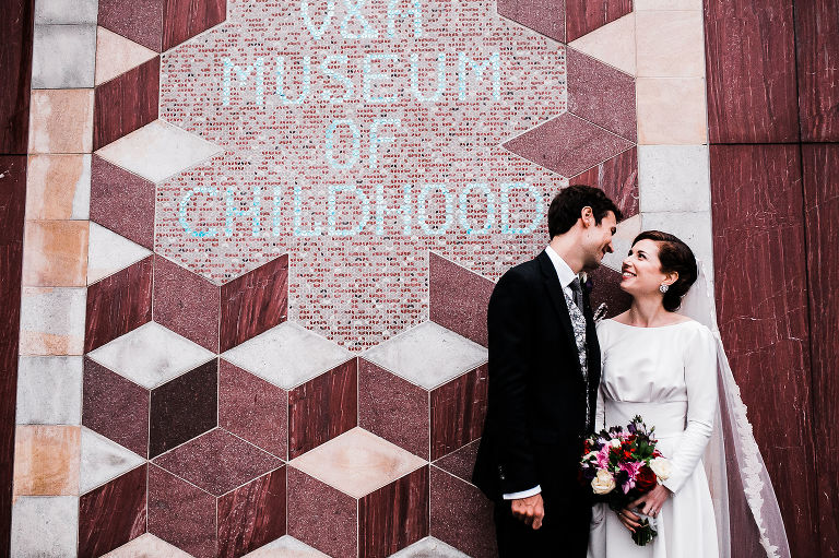 Bride and groom by the V&A wall in London