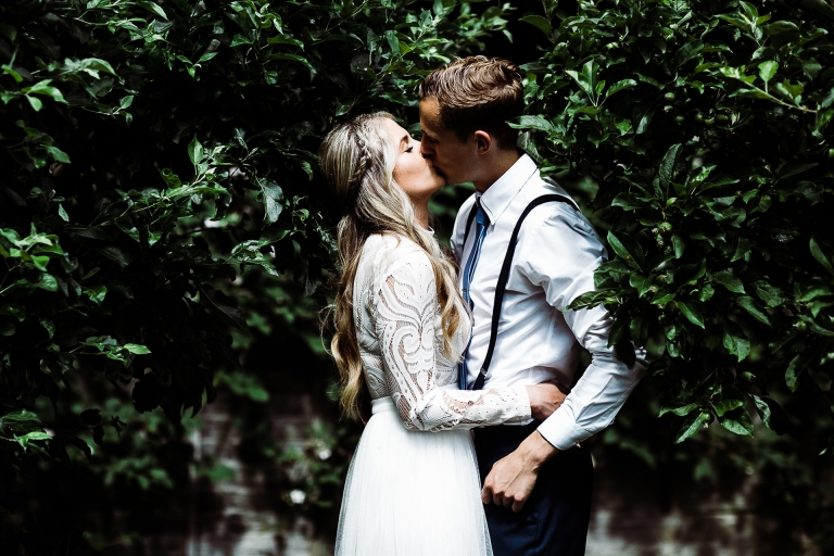 Bride and groom kissing in their garden
