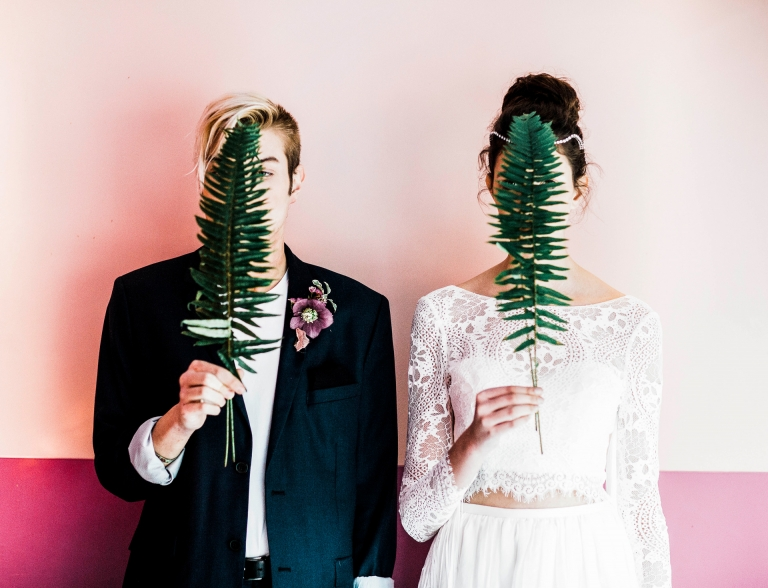 A bride and groom holding a fern at Rascals resturant