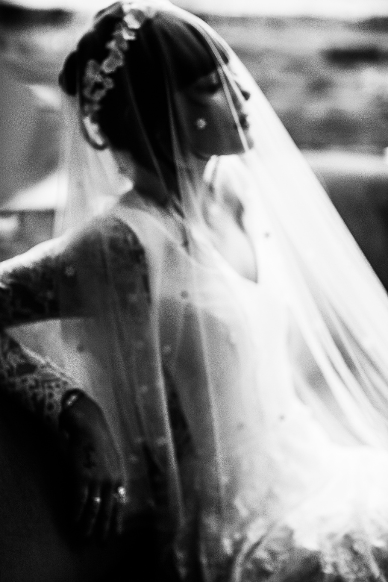 Bride looking away in a veil at the secret garden Kent